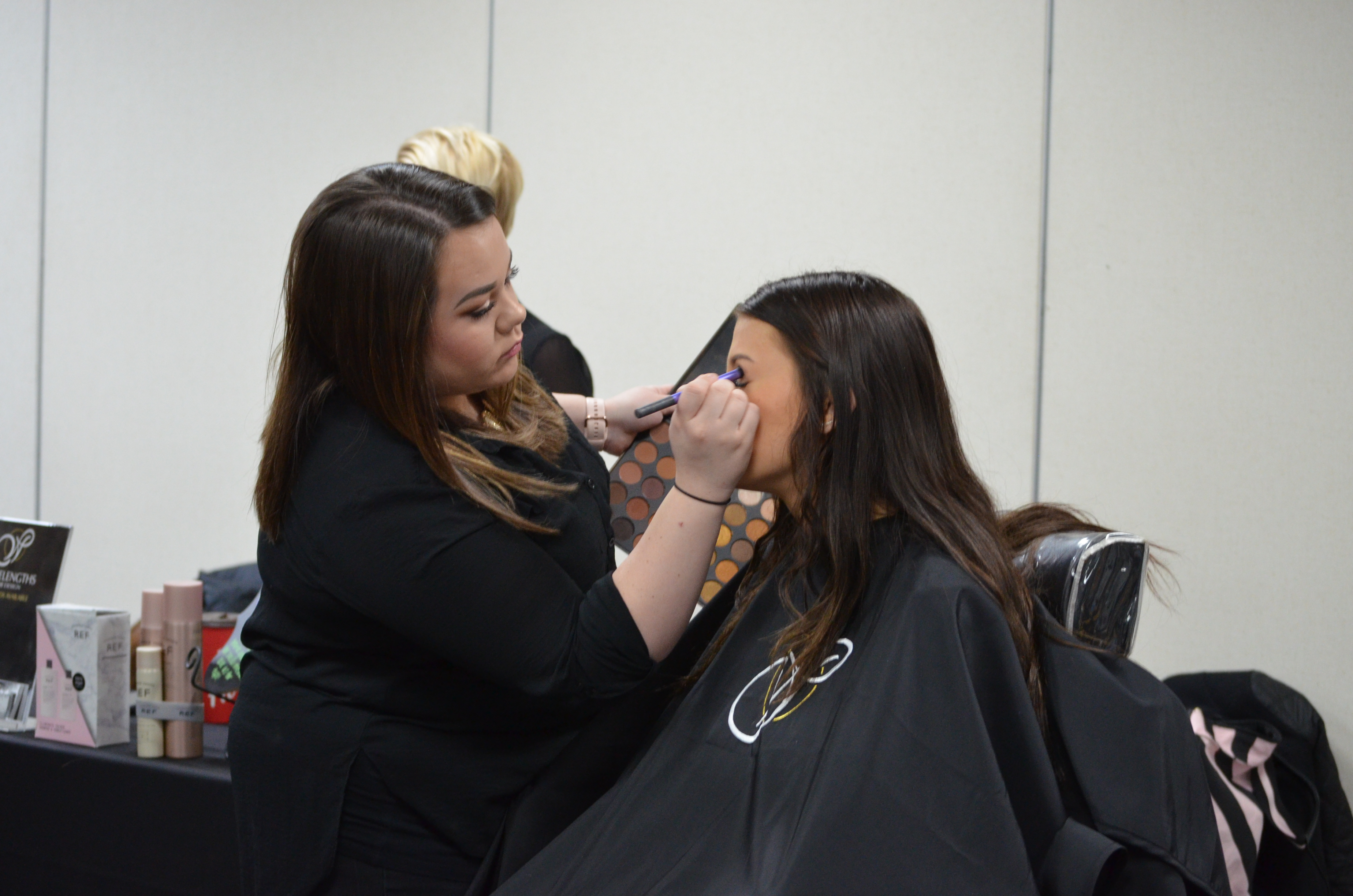 Jessica Hizer of Wavelengths Hair Design applies makeup to Keira Krantz, Kenmore East High School junior and first year cosmetology student at Kenton Career & Technical Center.