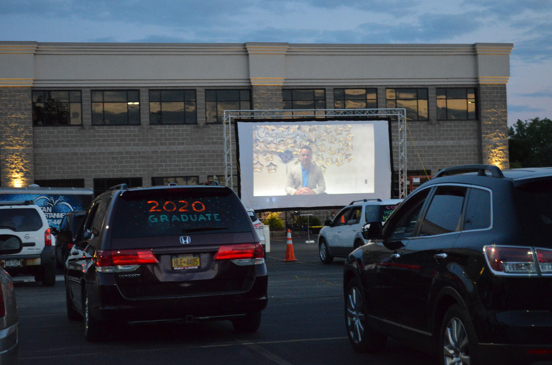 Families watch the drive-in graduation movie from their cars.