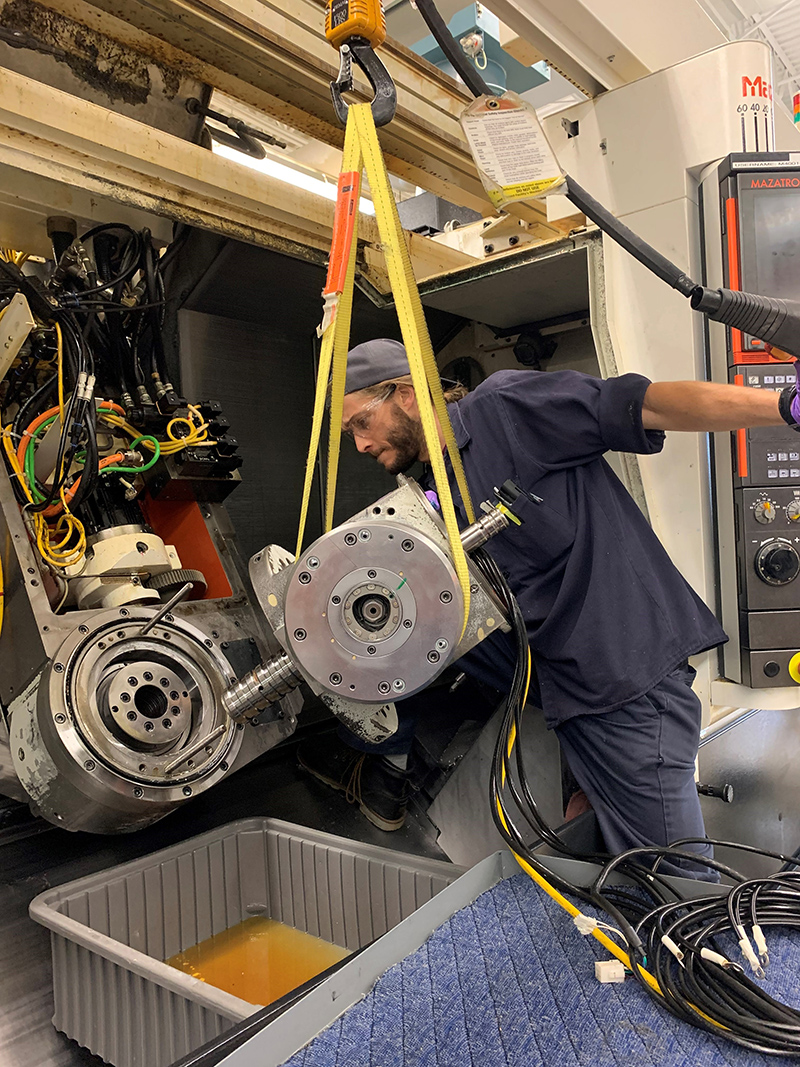 Bill Williams works to install a mill spindle on a machine.