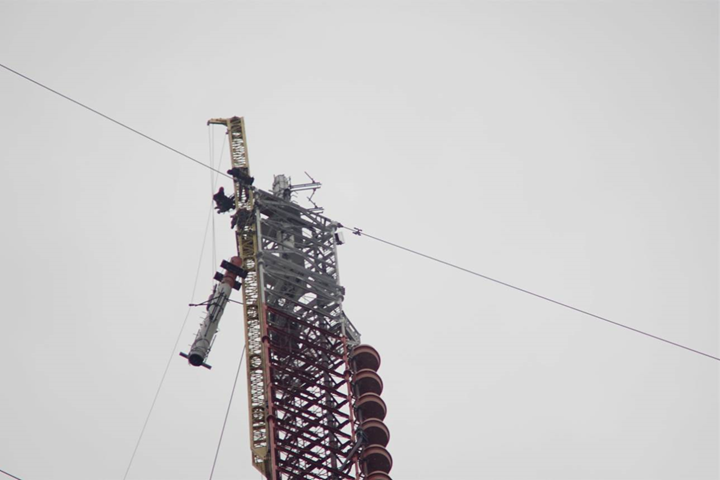 A tower crew works on removing a section of the old analog antenna at the Colden site.