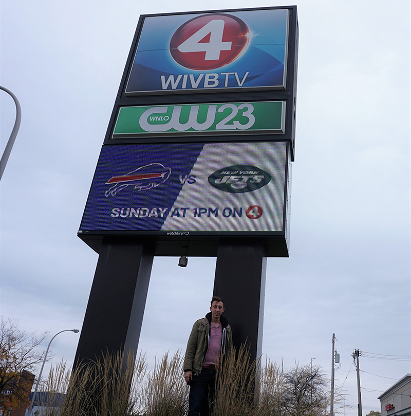 Chmiel stands in front of the WIVB-TV - CW-23 sign outside the studio.