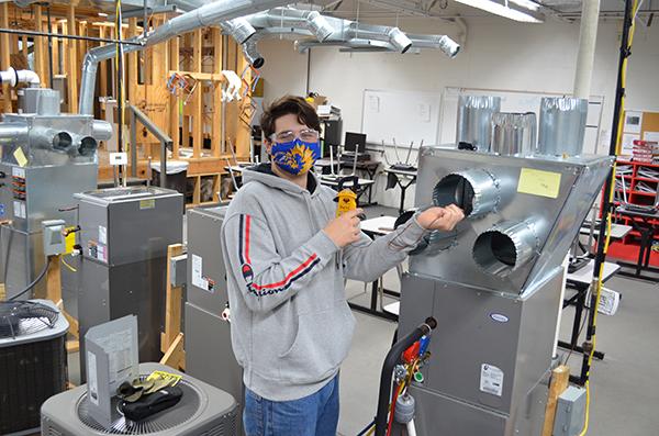 Brandon Miller works on an HVAC unit.